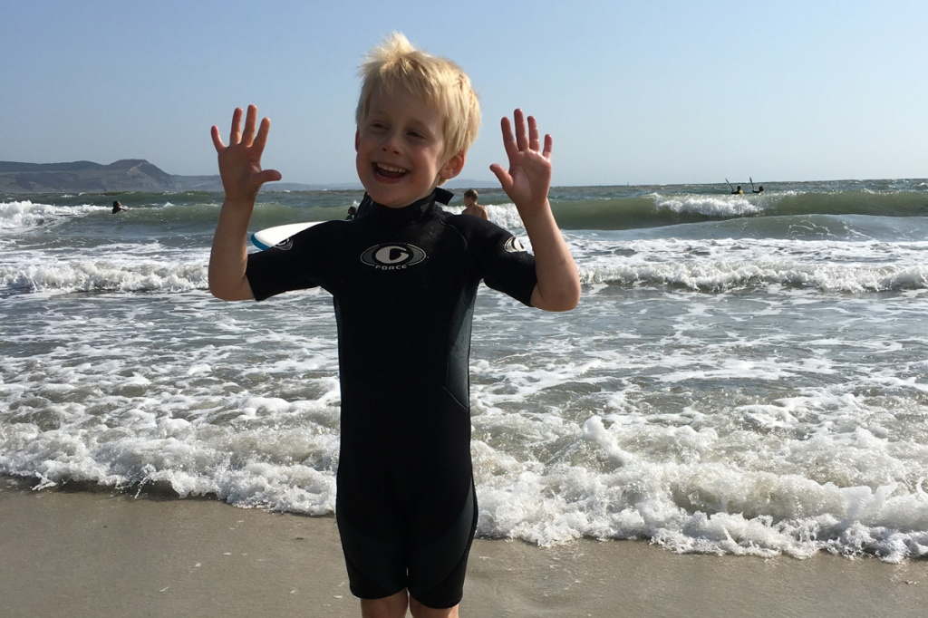 Boy standing on the beach in a wet suit