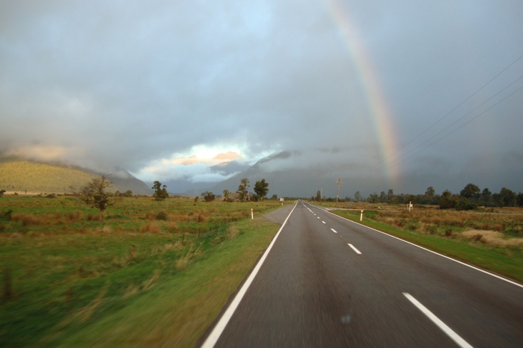 Driving through New Zealand - a rainbow over the road